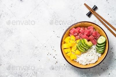 Tuna poke bowl with rice, avocado, mango and cucumber on white table
