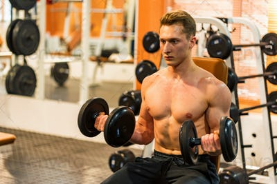 Attractive male athlete doing biceps exercise with dumbbells