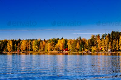 Autumn foliage, fall colorful forest over blue lake with red cabins in Finland.