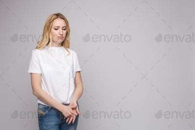 Upset young beautiful woman standing with crossed hands isolated at white studio background