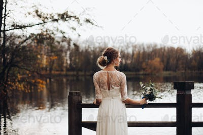 Elegant bride in white wedding dress with bouquet by lake