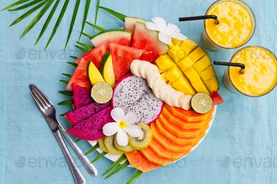 Tropical Fruits Assortment on a White Plate with Palm Tree Leaf with Mango Smoothie. Top View.