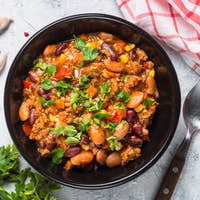 Chili con carne from meat and vegetables on stone table top view