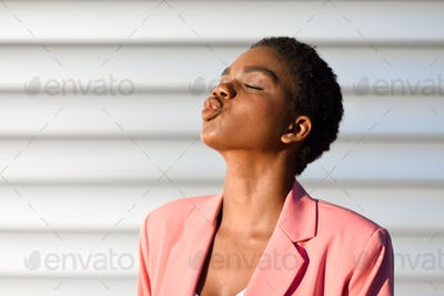 Black woman, with very short hair blowing a kiss