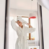 Young beautiful woman in white bathrobe and towel on head dreamily looking in mirror