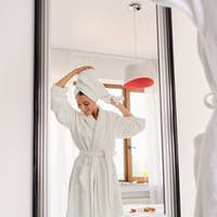 Smiling woman in white bathrobe and towel on head dreamily looking aside standing near mirror