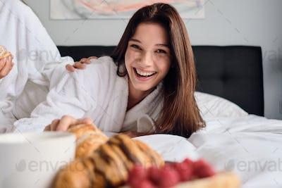 Girls having breakfast in bed in modern hotel