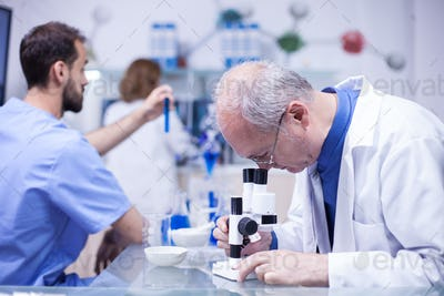 Senior technician making a discovery while working on microscope