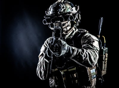 Army soldier aiming rifle in camera in darkness