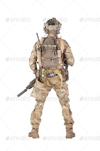 Armed army soldier standing backwards studio shoot