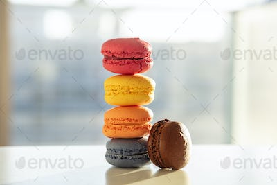 Colorful macarons pile on white background, close up view