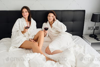 Two beautiful women in bathrobes holding glasses of red wine dreamily looking aside lying in bed
