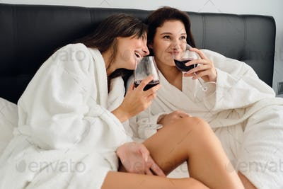 Two smiling women in white bathrobes lying in bed and joyfully drinking wine in modern hotel