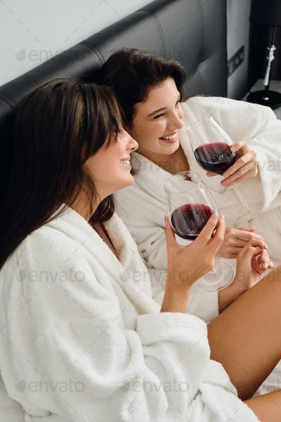 Two pretty cheerful women in white bathrobes happily lying in bed with glasses of red wine in hands