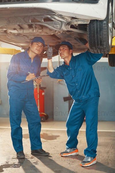 Car mechanics inspecting problems