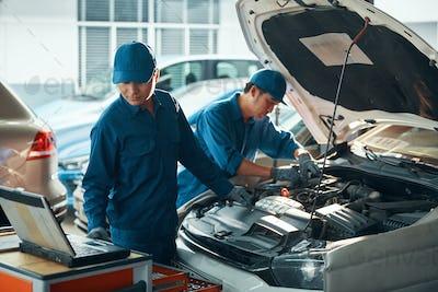 Garage workers repairing car