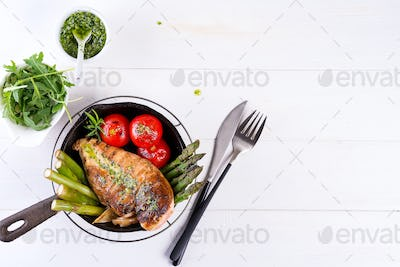 Grilled chicken breast on a cast iron skillet with grill vegetables and green sauce on a white