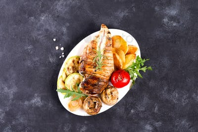 Grilled chicken breast on a plate with tomatoes, mushrooms on a stone background, flat lay