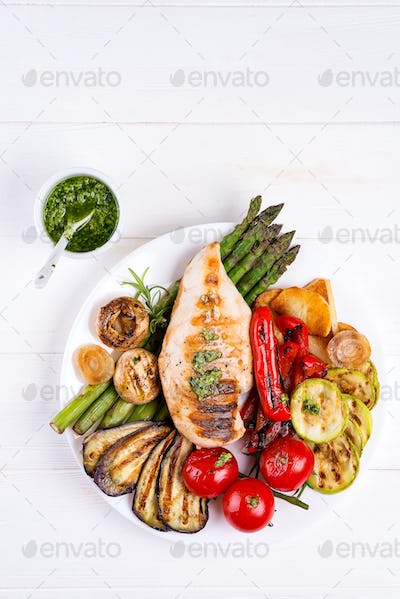 Grilled chicken breast on a plate with grill vegetables on a wooden background, flat lay