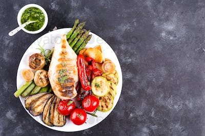Grilled chicken breast on a plate with tomatoes, asparagus and mushrooms on a stone background, flat