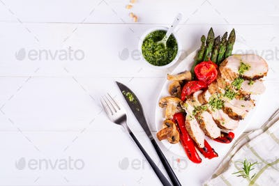 Grilled chicken breast on a plate with tomatoes, asparagus and mushrooms on a wooden background