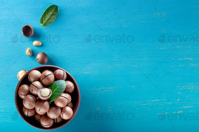 Macadamia nuts with leaf in plate and scattering on blue background
