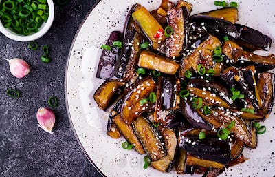 Hot spicy stew eggplant in Korean style with green onion. Aubergine saute. Vegan food. Top view