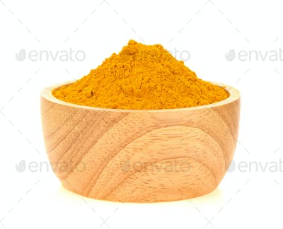 Turmeric powder in wood bowl on white background.