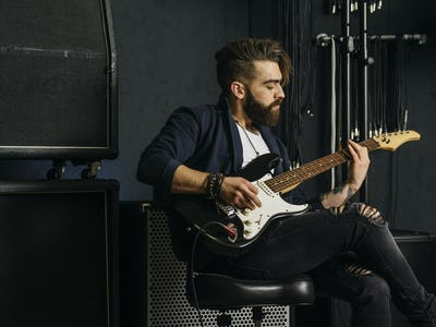 Bearded man playing guitar in a music studio