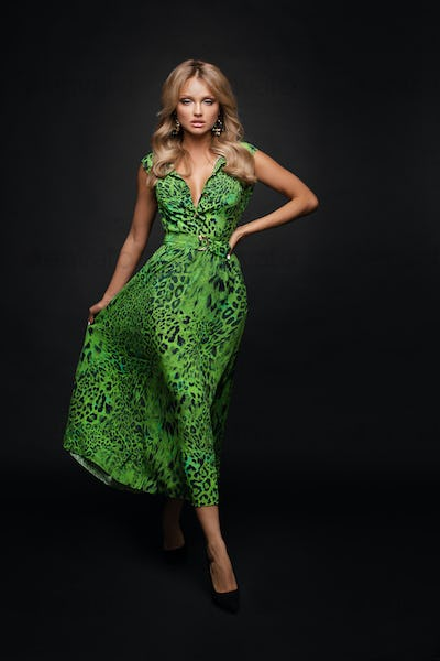 Slim blonde in green dress on black isolated background