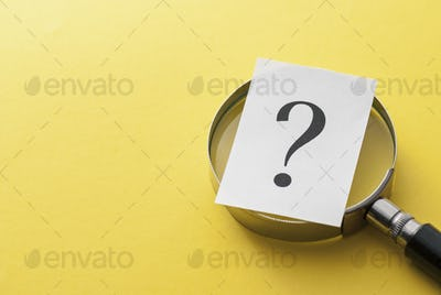 Printed question mark covering a magnifying glass