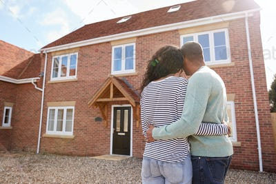 Rear View Of Couple Standing Outside New Home On Moving Day Looking At House