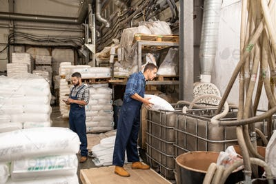 Young workers of large factory scattering polymer grains into huge container