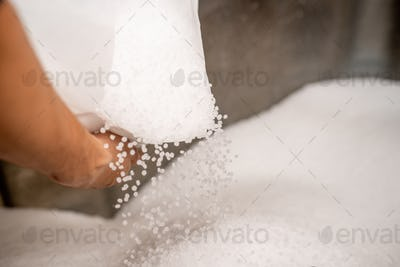 Small plastic granules scattering out of white sack held by worker