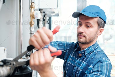 Contemporary young mechanic from household maintenance service repairing pipe