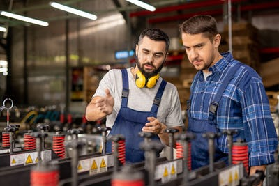 Two young men checking new industrial processing equipment