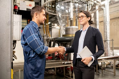 Young female partner shaking hand of engineer of chemical processing factory