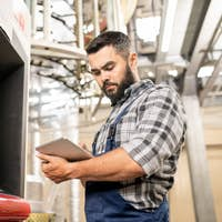 Bearded young worker of polymer production looking through data in touchpad