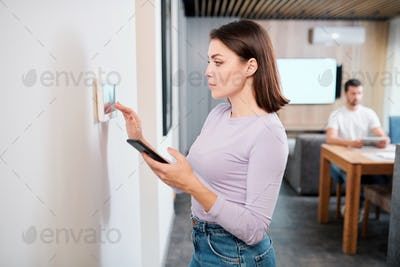 Young woman with smartphone loading smart remote control application in touchpad