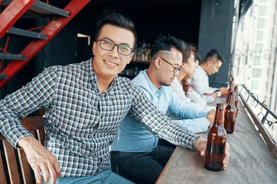 Businessman drinking beer at bar