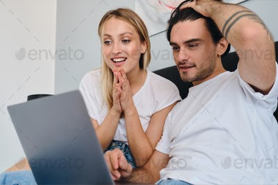Young man and pretty smiling blond woman joyfully using laptop together sitting on bed