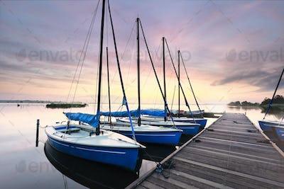 few yachts by pier at dawn