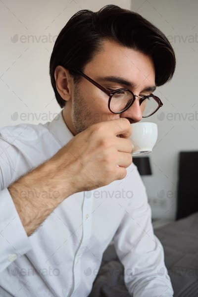 Young attractive man in white shirt and eyeglasses sitting on bed dreamily drinking coffee in hotel
