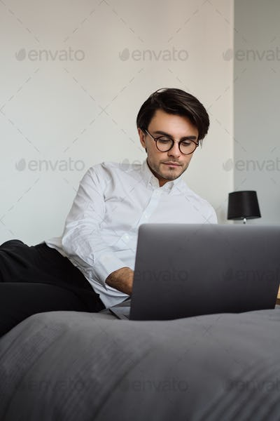 Young beautiful man in white shirt and eyeglasses lying on bed thoughtfully working on laptop