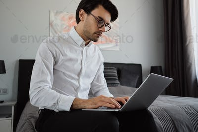 Young attractive man in white shirt and eyeglasses sitting on bed thoughtfully working on laptop