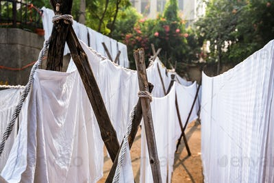 White sheets hang on ropes in Indian street