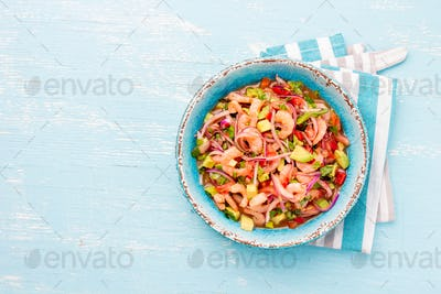 Mexican shrimps ceviche sebiche with tomatoes and avocado in blue bowl, wooden blue background.