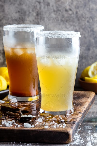 Two types of latin american beer drink Michelada with lemon juice and salt.