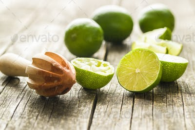 Wooden citrus squeezer and green lime.