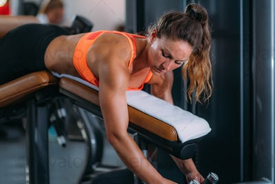 Female Athlete Exercising at Lying Leg Curl Bench in The Gym